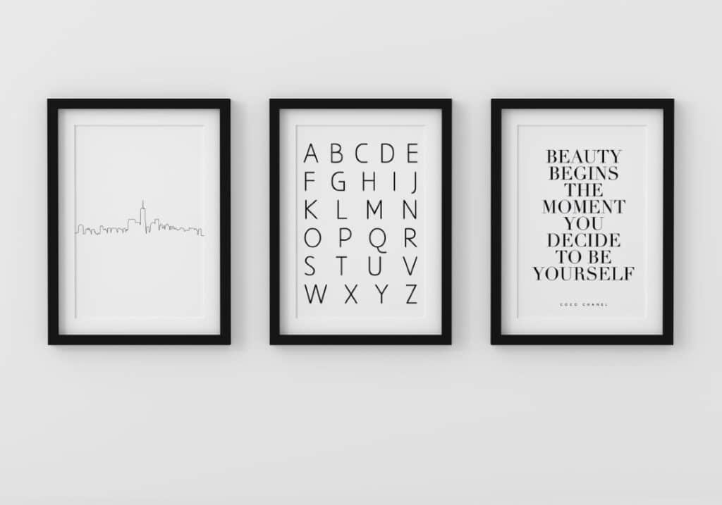 Set of three minimalist black and white wall art prints in frame on wall