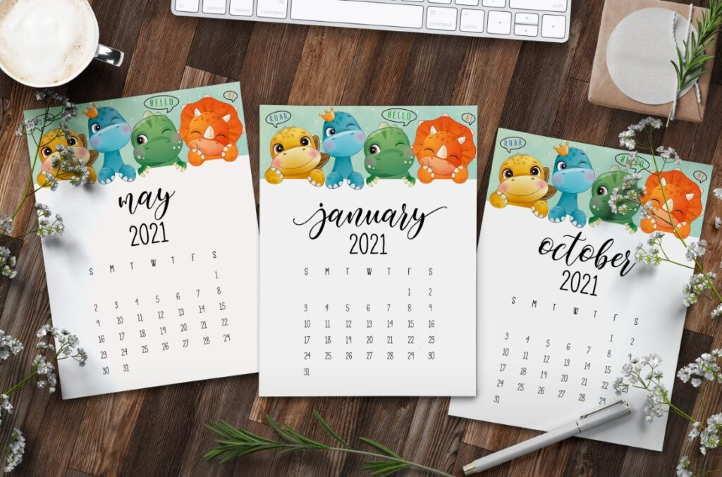 Set of three printable calendars on desk, with cute dinosaurs and text overlay - free printable 2021 calendar